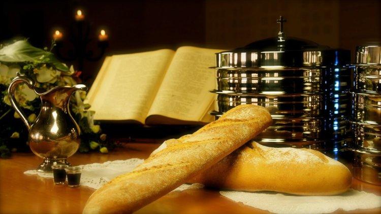 Symbolbild Abendmahl: Brot vor Wein und einer offenen Bibel