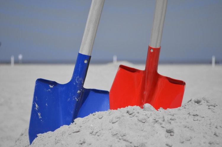 """Symbolbild """"Suche nach Leben"""". 2 Schaufeln im Sand"""