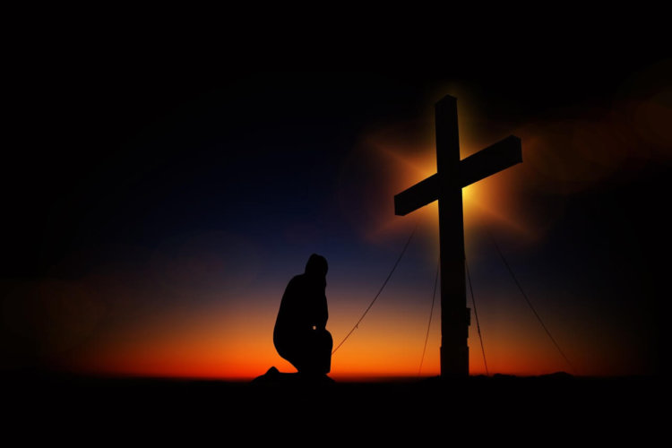 """Symbolbild: """"Kniend Beten"""": Schatten eines knienden Mannes vor einem Kreuz."""