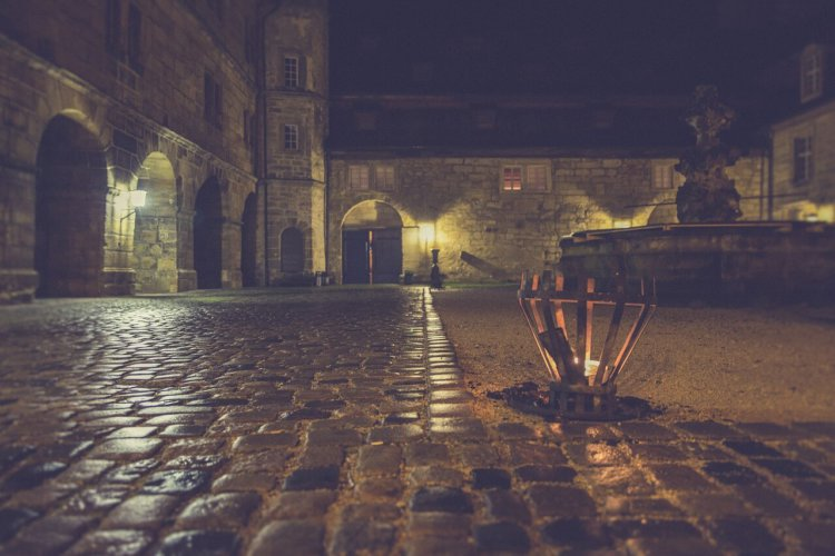 """Symbolbild für Psalm 130,6: """"Meine Seele wartet auf den Herrn mehr als die Wächter auf den Morgen."""": Innenhof einer Burg im Dunkeln."""
