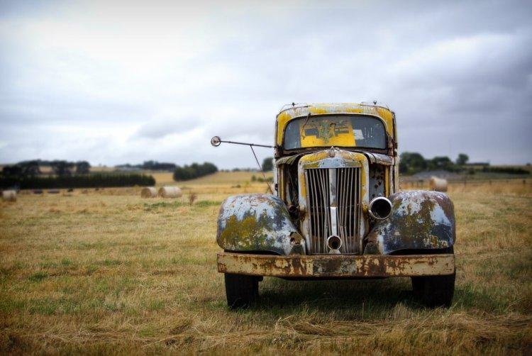 """Symbolbild: """"Vergiss nicht deinen Gott"""". Ein verrostetes, vergessenes Auto auf einem Feld"""