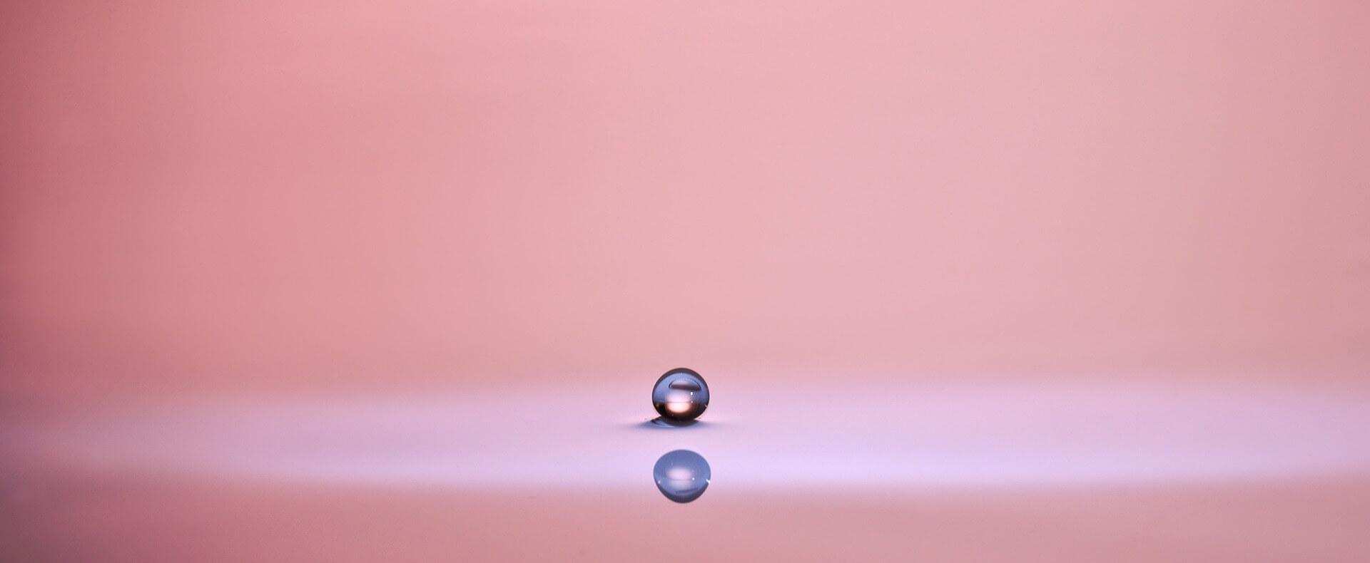 """Symbolbild zur Predigt """"Schatz im Acker - köstliche Perle"""": Spiegelnder Wassertropfen, ähnlich eine Perle vor hellem, leerem Hintergrund"""