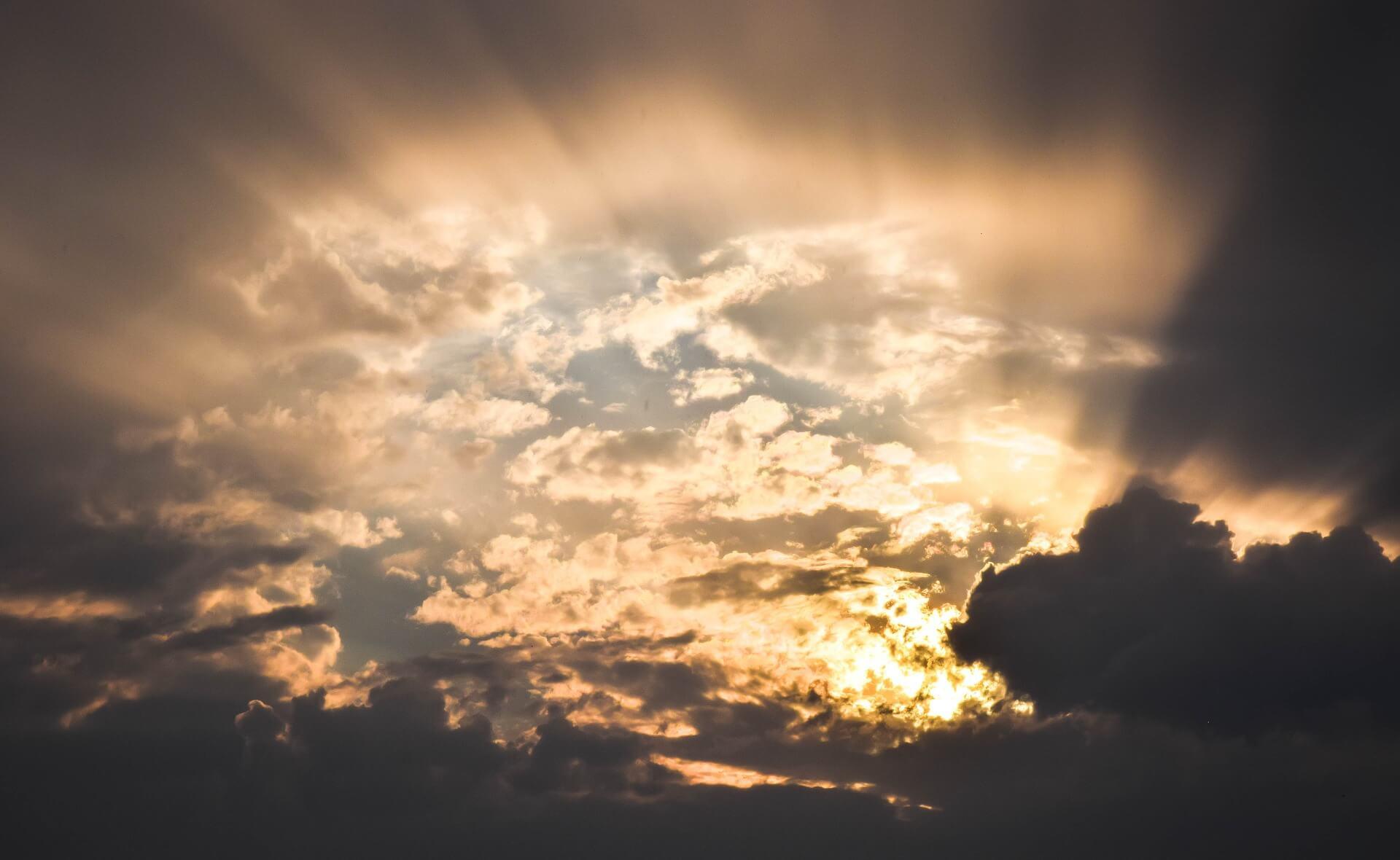 """Symbolbild """"Gemeinde ist die Hoffnung der Welt"""" - Wolken mit Sonne im Hintergrund"""