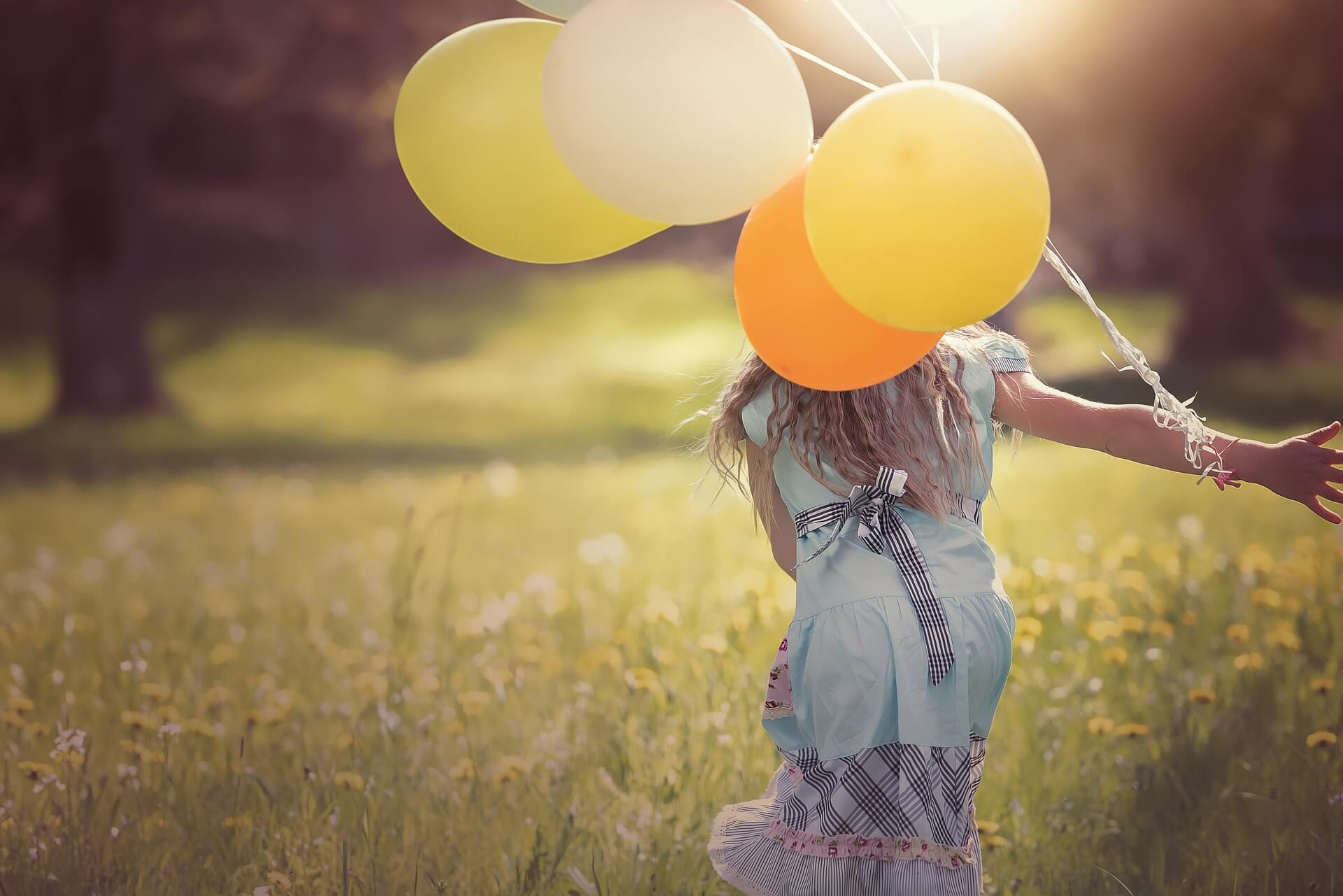 Freude: Ein Mädchen mit Luftballons in Sonnenschein
